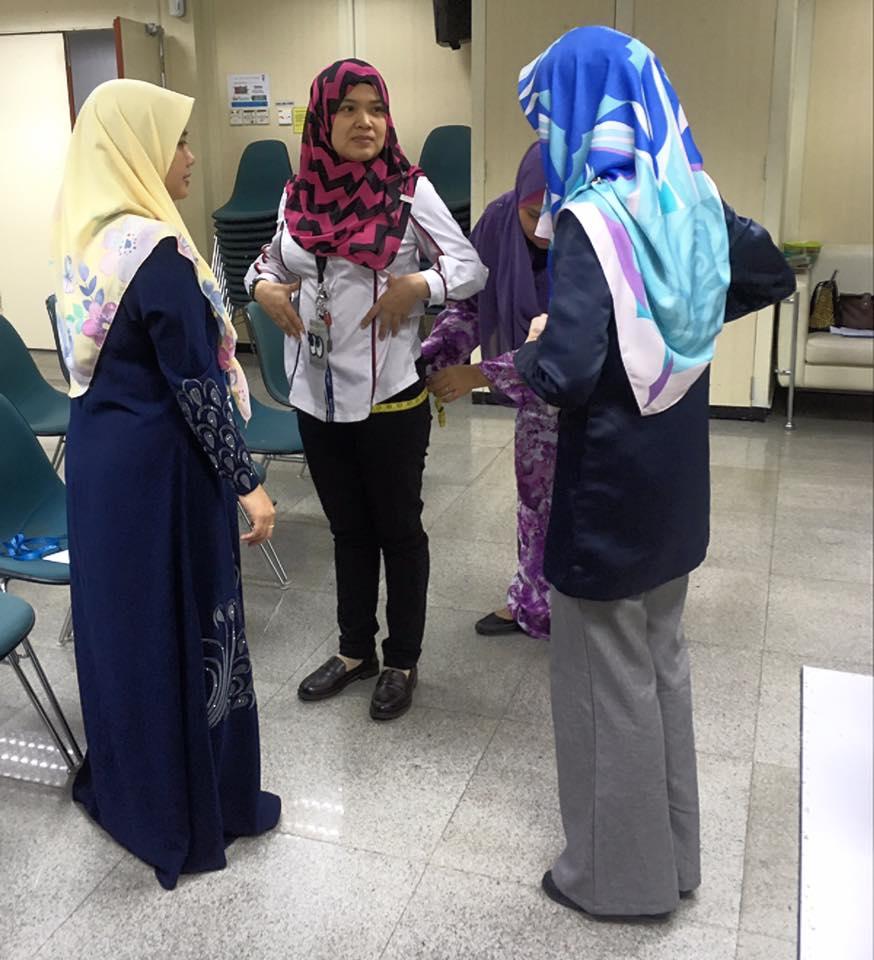 Puan Raihan membantu peserta bagaimana mengambil ukuran badan dengan teknik yang betul